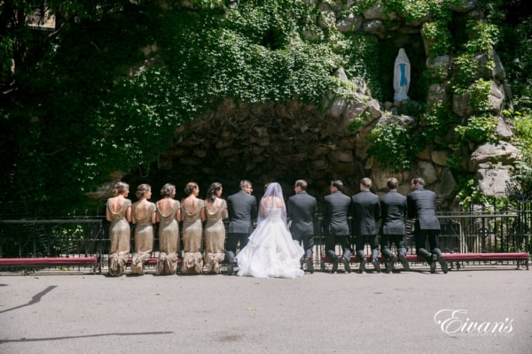 The couple and their counterparts kneel in front of a beautiful wall with lots of gorgeous ivy.