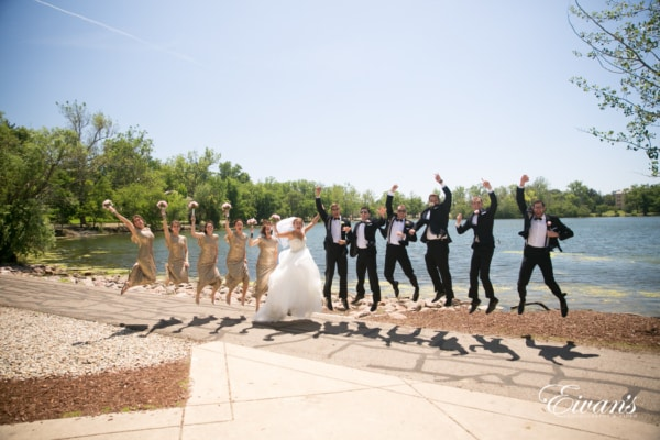 The groom and bride with their closest friends jump and smile with lots of joy and only happiness.