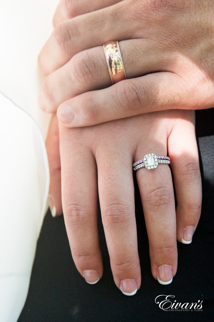 Holding hands, the now husband and wife show off their rings that show their solidified love.