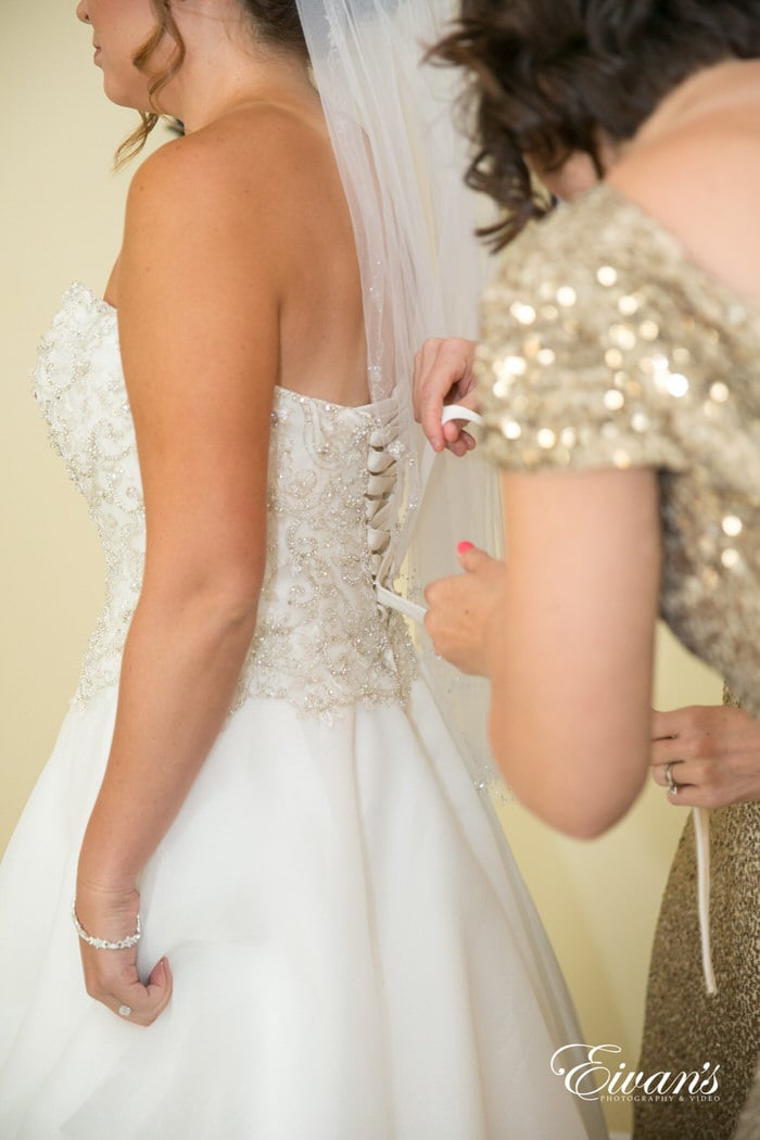 The bride is having her intricate and beaded gown laced up onto her by her beautiful bridesmaids.