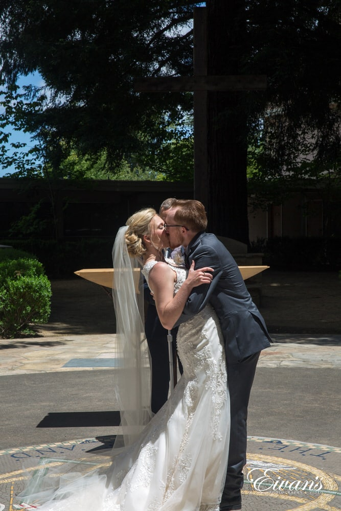 "The couple kiss romantically at the alter after they seal their ""I do's"""