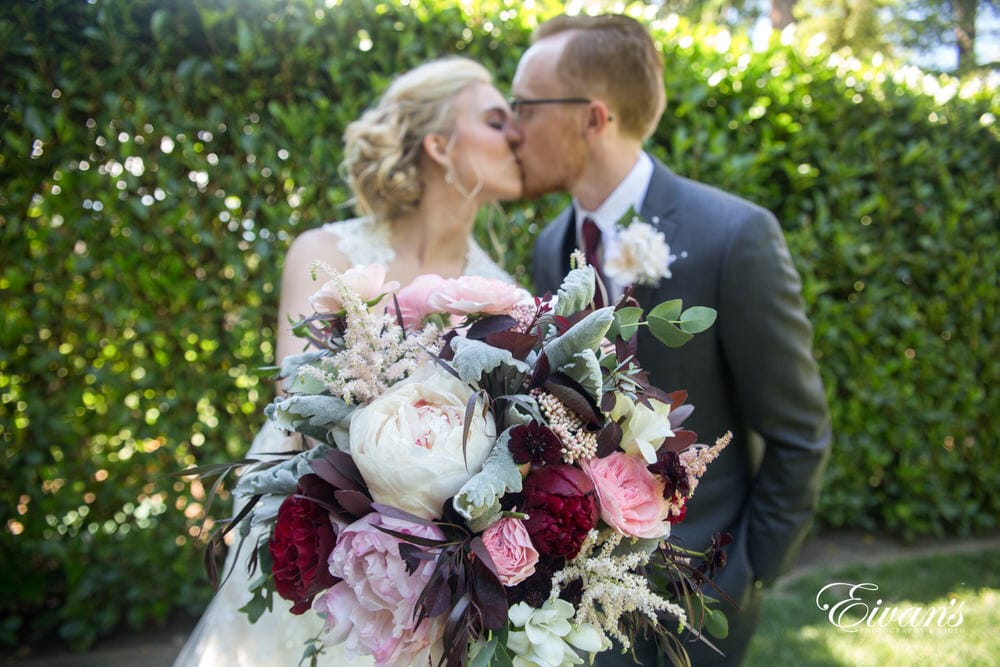 Holding her vintage and stunning maroon and pink floral bouquet with them kissing and celebrating themselves and their marriage.