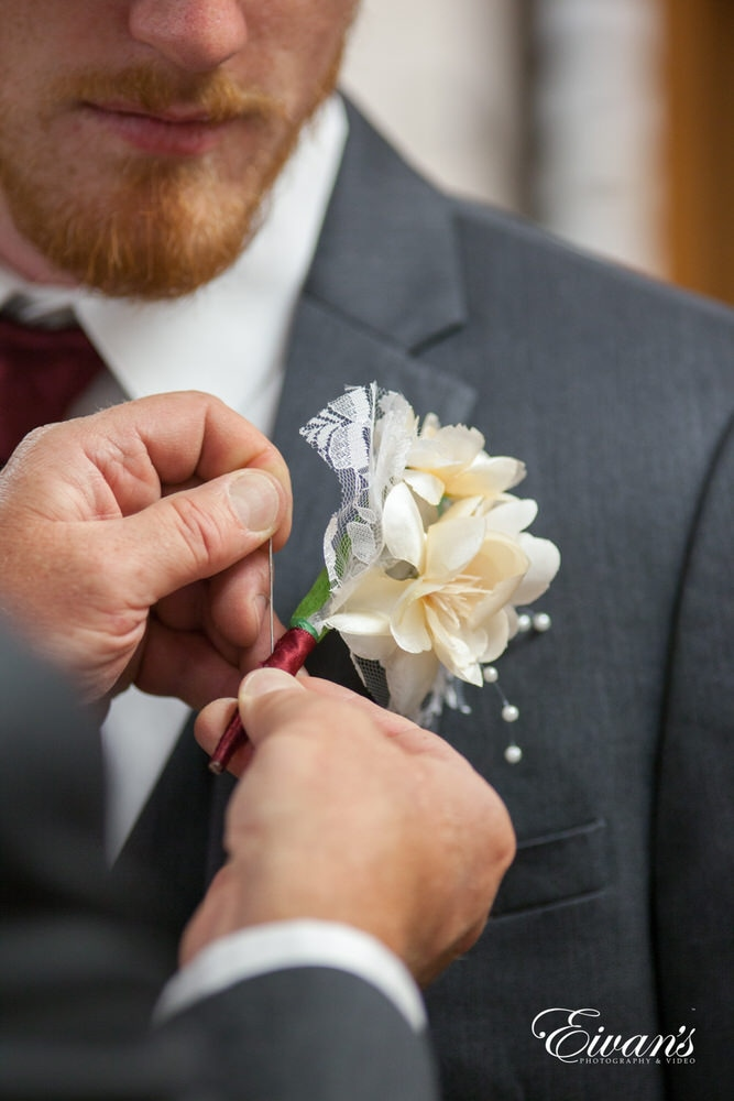 Pinning a wonderful floral boutonniere to complete the groom's entire ensemble.