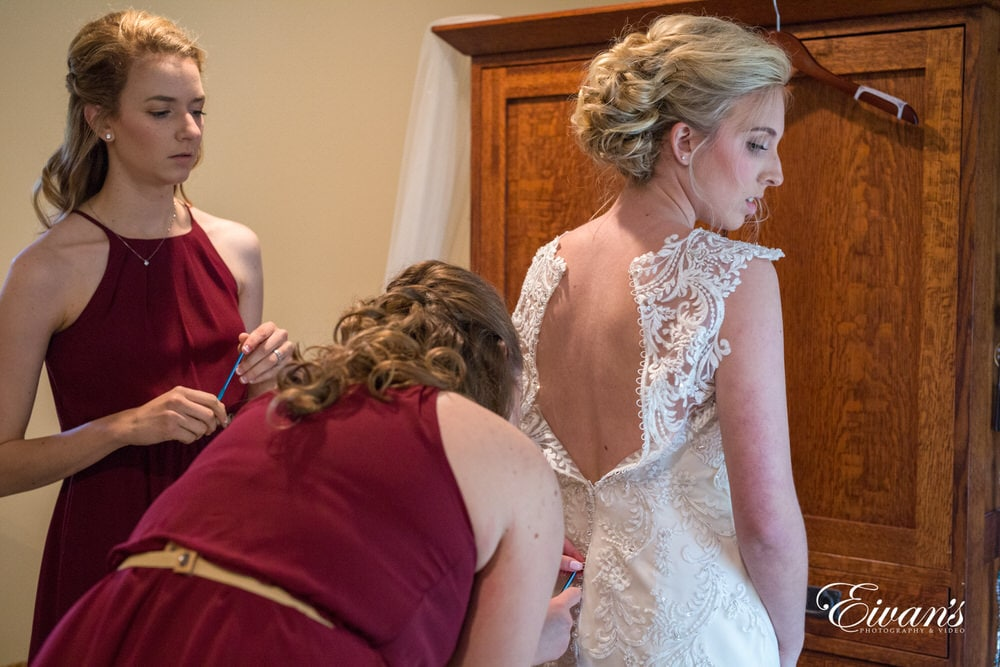 The bridesmaids help zip the bride into her stunning wedding dress that is just so perfectly fitting on her.