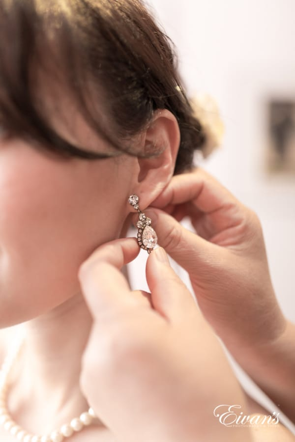 The sparkling diamond earrings are glistening in this photograph where you can see the amazing jewelry this bride wore on her special day.