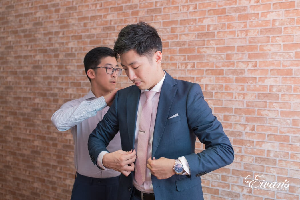 In this photograph, the groom is putting on his fabulous navy blue suit with a light pink tie.