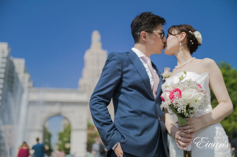 The groom and bride kiss and demonstrate their love in front of everyone and the gorgeous city