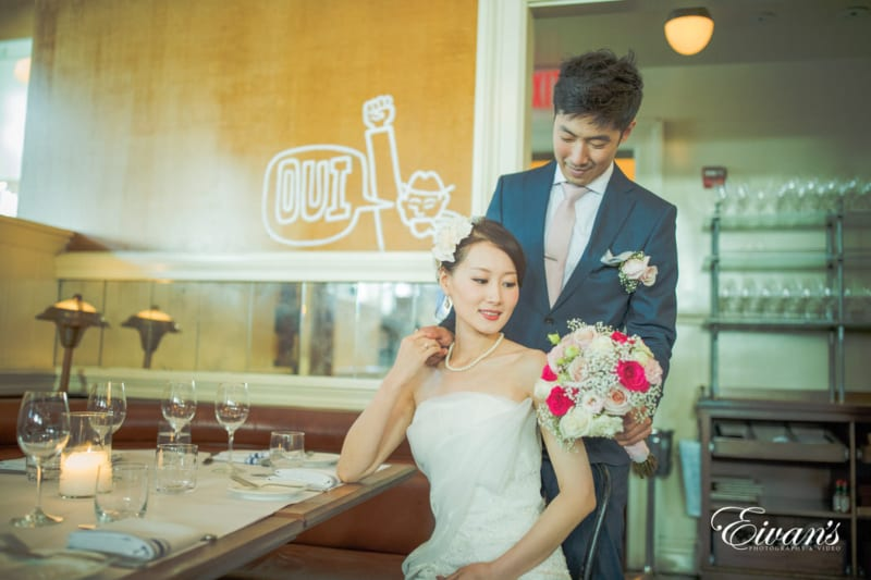 The groom hands his bride a white and pink rose bouquet as she sits of so elegantly at a lovely table.