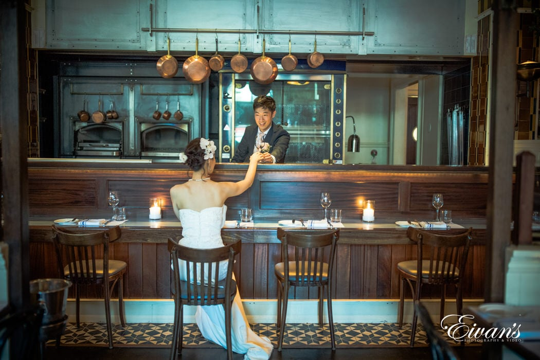 The groom serves a drink to the love of his life at a modern bar with a classic yet elegant twist.