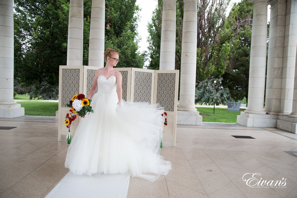 The bride's dress is flying up so elegantly just showing how classic she looks.