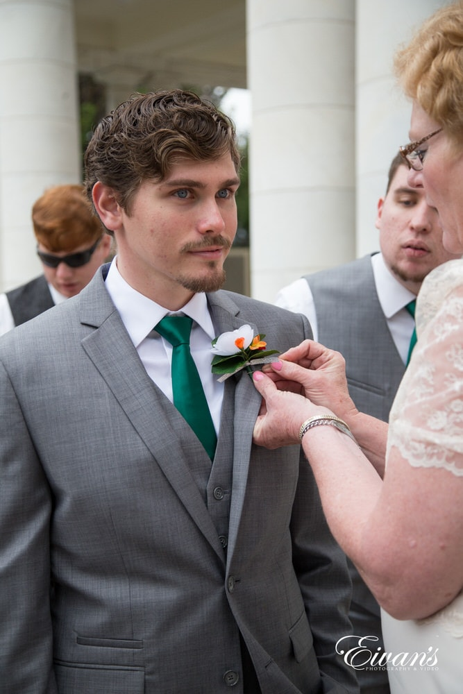 The groom prepares to see his bride at the end of the isle by having someone put on his boutonniere.