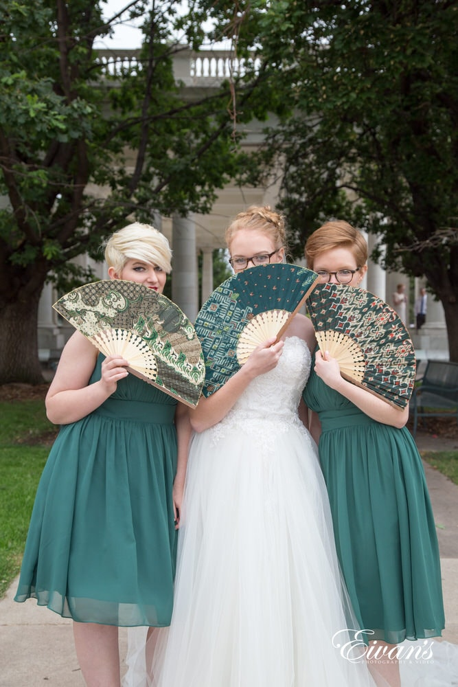 The bride and her bridesmaids hide behind some beautiful fans that tie together with the weddings color theme.
