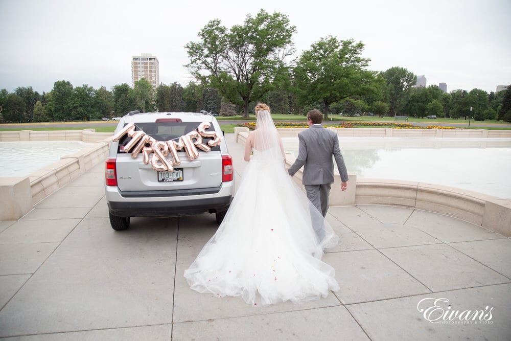 The bride and groom drive off in their jeep 4x4 after finally getting married.