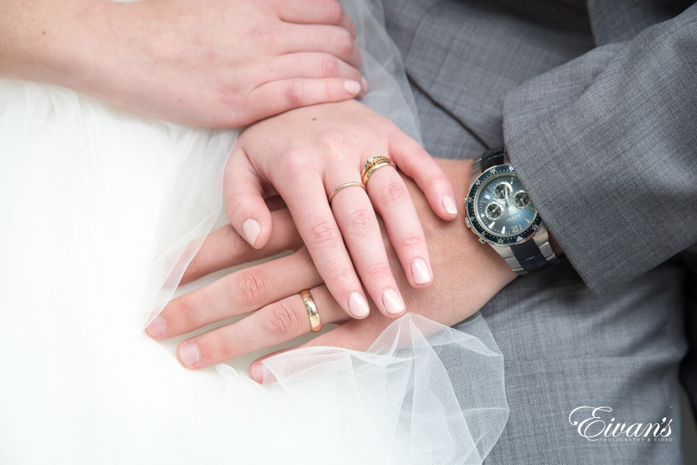 The bride and groom hold hands showing off their beautiful rings that solidify their love.
