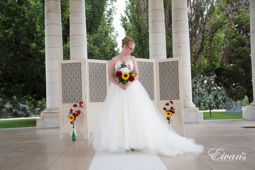 The bride stands looking absolutely stunning in her pearly white bridal gown.