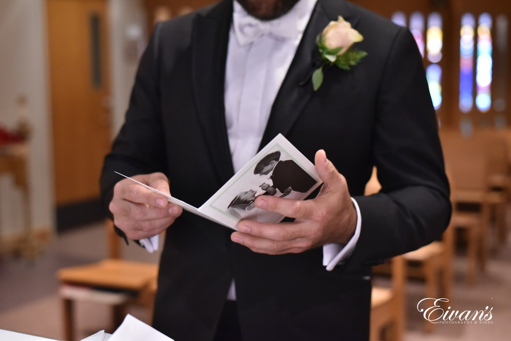 The groom reads a card right before his gorgeous bride surprises him in her ravishing look.
