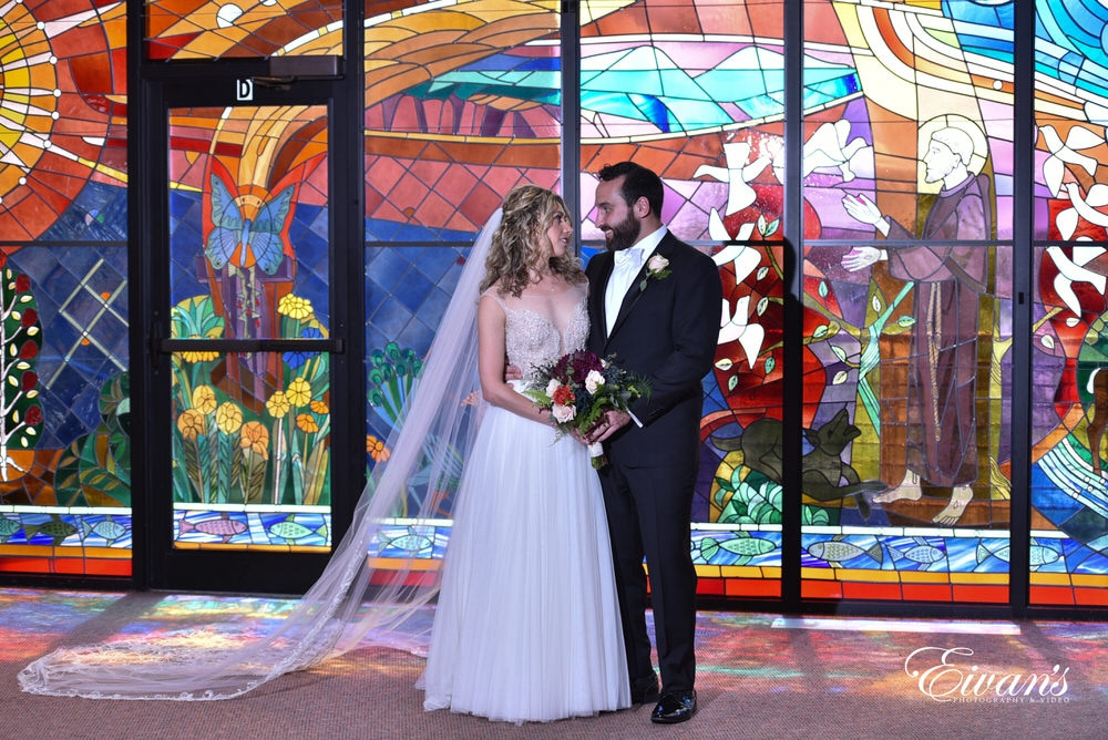 The stain glass only enhances this couple's love as they stand in front of an intricate and stunning window.