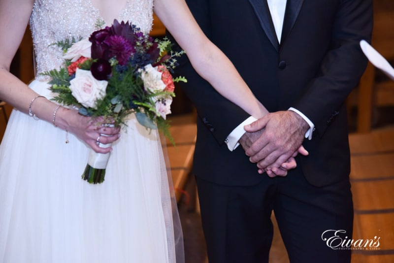 The groom holds his bride's while standing at the alter together.