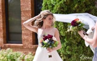 The bride smiles beautifully as her bridesmaids help elegantly arrange her veil.