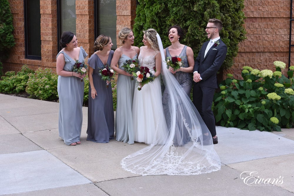 The bride and her counterparts smile and laugh together simply enjoying the other's company.