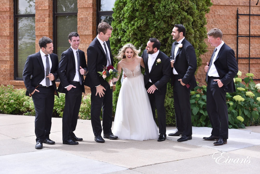 The bride intercepts the groom and his groomsmen with lots of laughter and a thousand smiles.