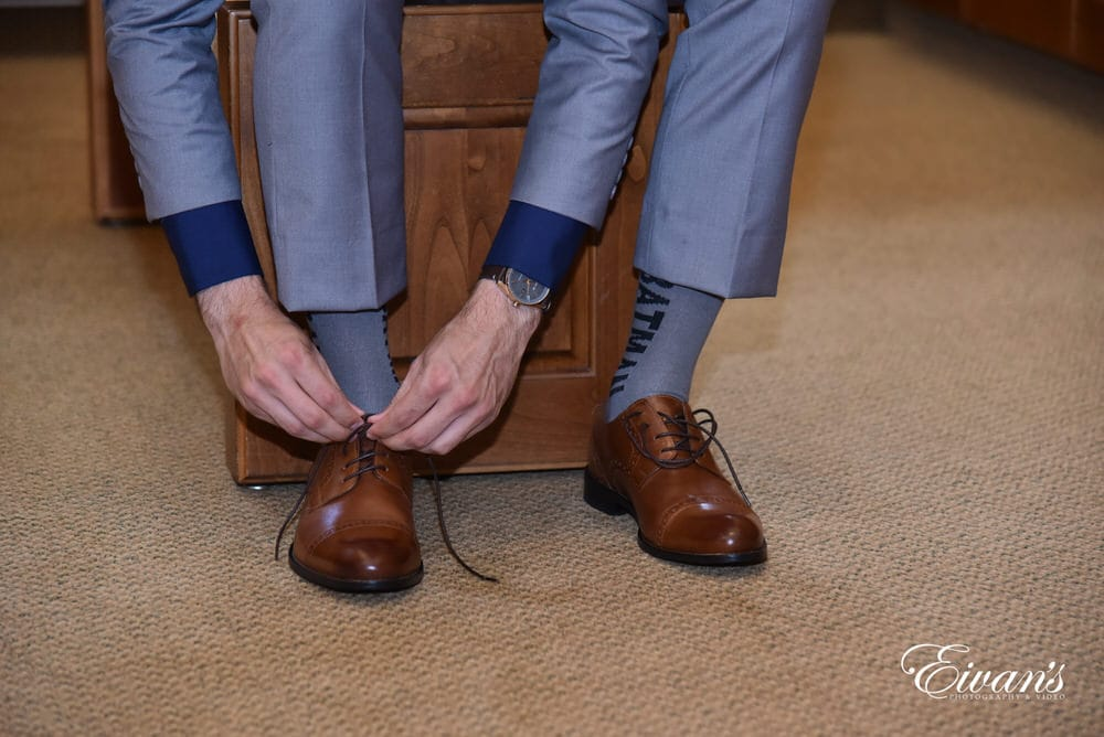 The groom lace his brown leather shoes prepping for the last time he will ever be single.