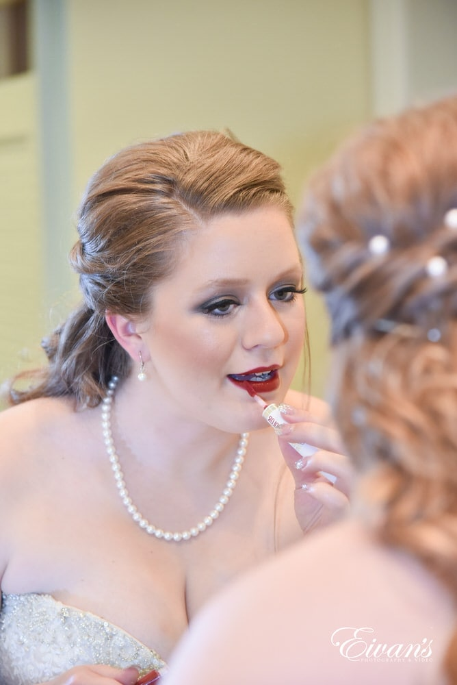 The bride puts on her dramatic red lipstick ready for such a fantastic wedding.