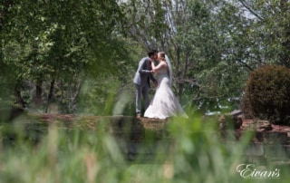 The couple kiss in the beautiful and thriving nature environment.