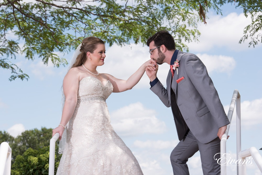 The groom kisses his bride's hand showing that chivalry is not dead.