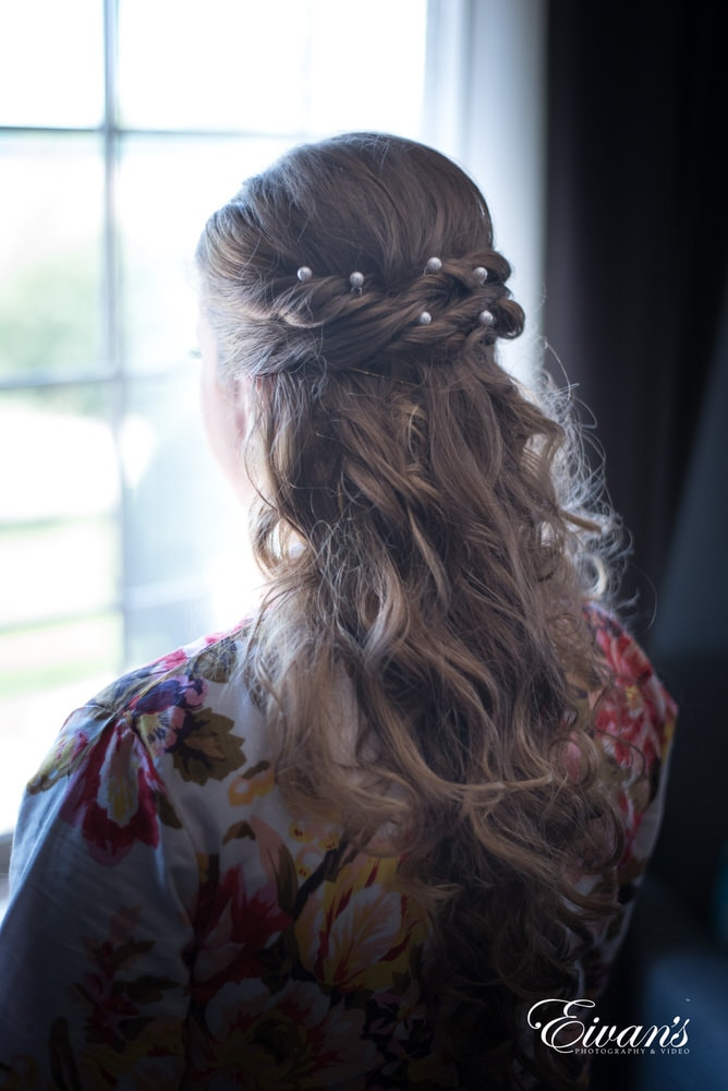 The bride's hair is put up into a half-up-and-half-down style with pearls placed between her twisted braids.