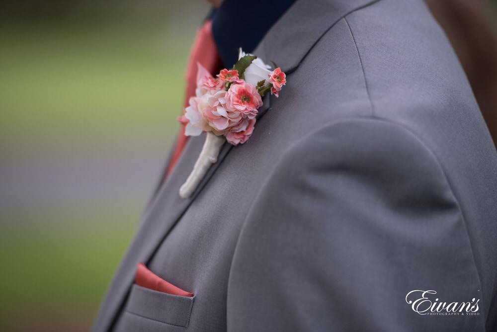 The groom wears a peachy pink floral boutonniere.