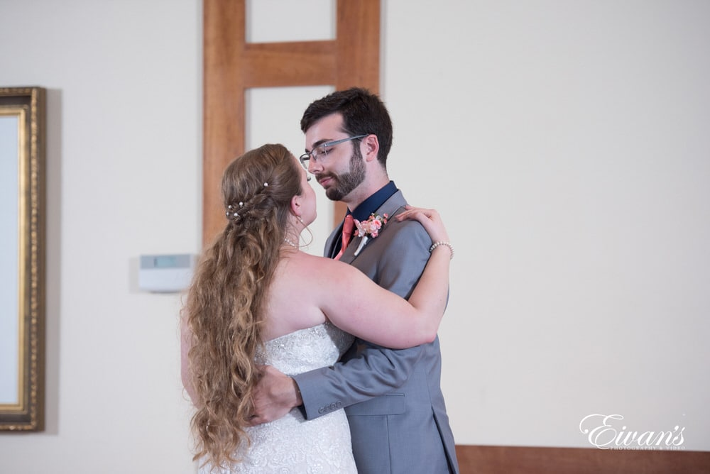 The couple hold one another while sharing their first dance.