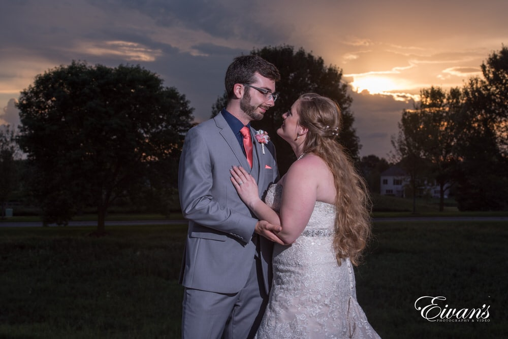 The bride and groom stand overshadowing the beautiful sunset.