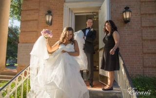 The groom helps carry his bride's gown down the steps as they exit the chapel.