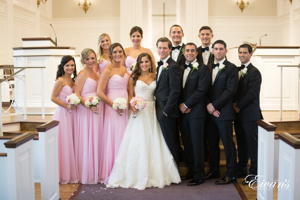 The bridal party all stand together within the halls of this pearly white chapel.