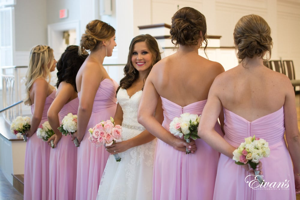 The bride stands with her closest counterparts while beaming with happiness.