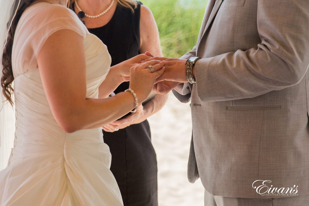 The bride and groom slip their wedding bands onto one another's fingers making their love official.