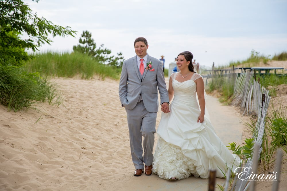 The couple walk together along the beachside, hand-in-hand celebrating their new found marriage.