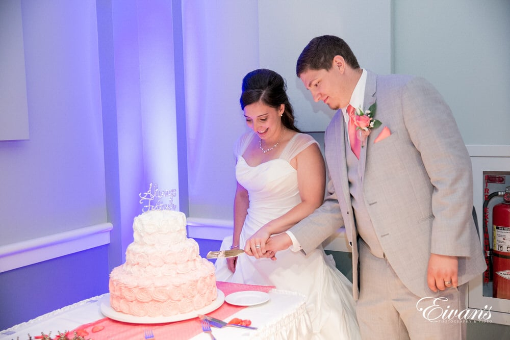 The bride and groom cut into their delicious and elegant wedding cake together.