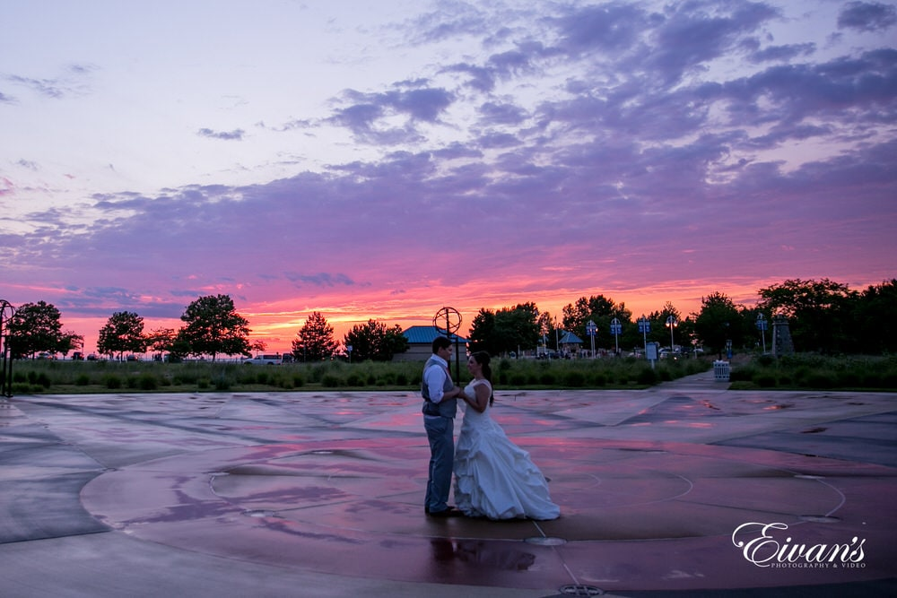 The bride and groom stand in a beautiful park with a vibrant and exquisite sunset in the background.