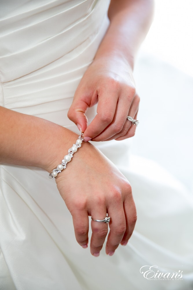 The bride adjusts her bracelet while preparing to walk down the isle to the one she loves.
