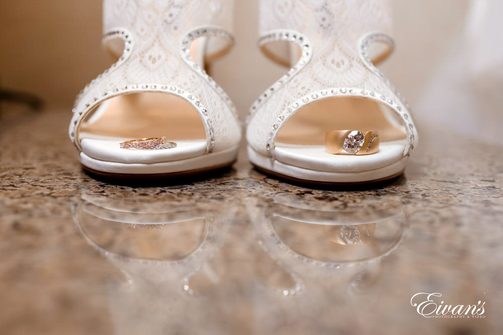 The bride's open-toed cream shoes hold the rings that will soon be on the fingers of the newly wed couple.