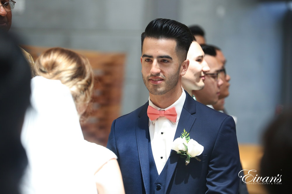 The groom looks into the eyes of the bride as they solidify their vows and love to one another.