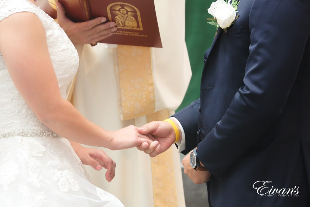 The couple hold one another's hands for the last time before they become one happily married couple.