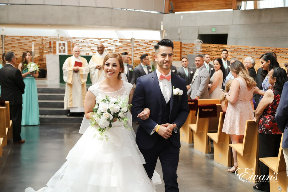 The bride and groom beam excitedly while they exit this beautiful chapel.