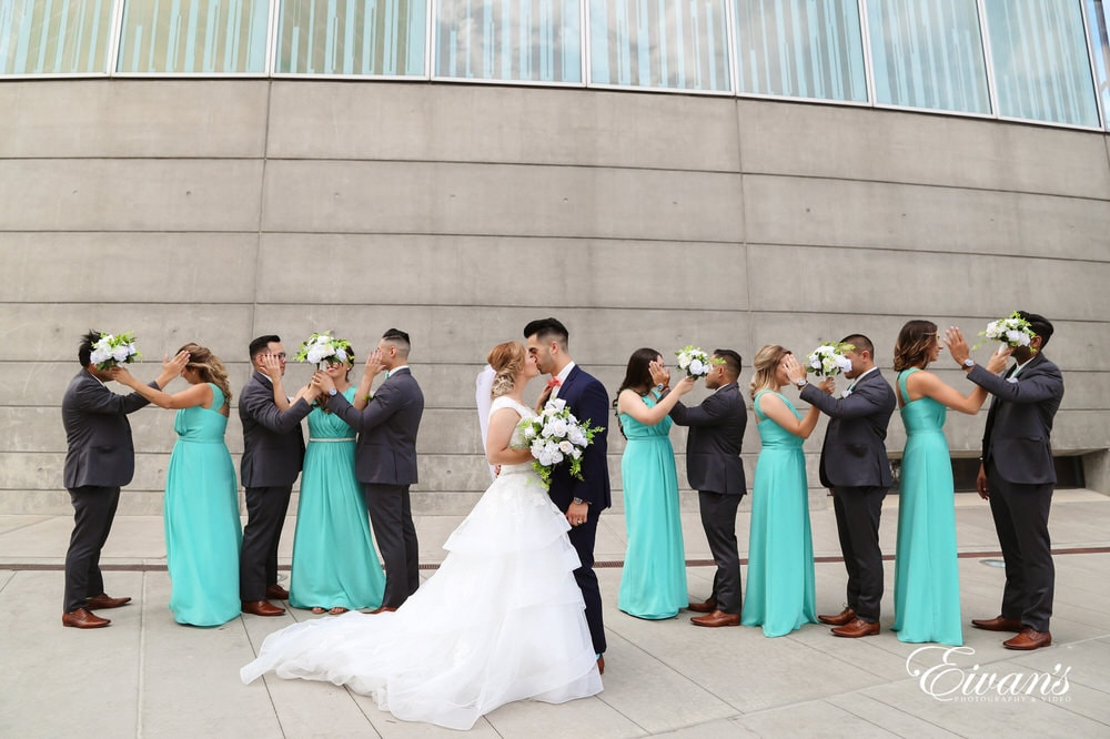 The bride and groom kiss one another's while their bridesmaids and groomsmen cover their eyes in the background.