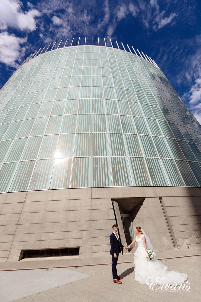 The bride and groom hold hands while standing in front of a stunning and amazing building.