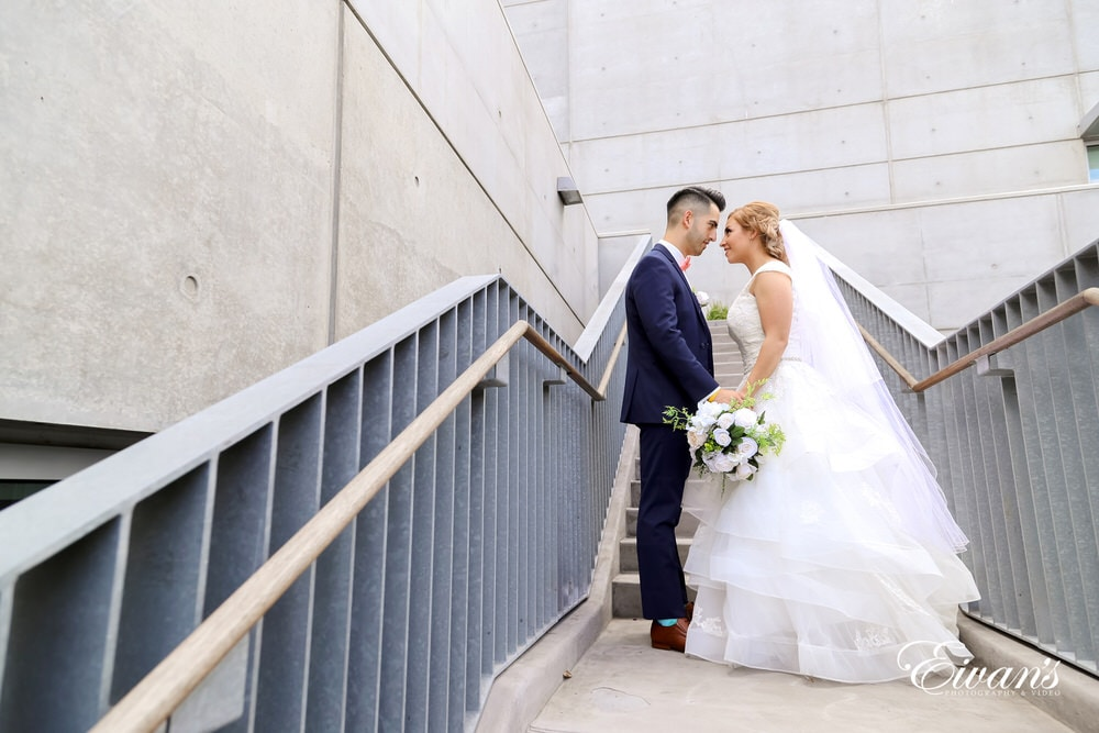 The bride and groom hold one another while standing on a stunning and beautiful stairwell.