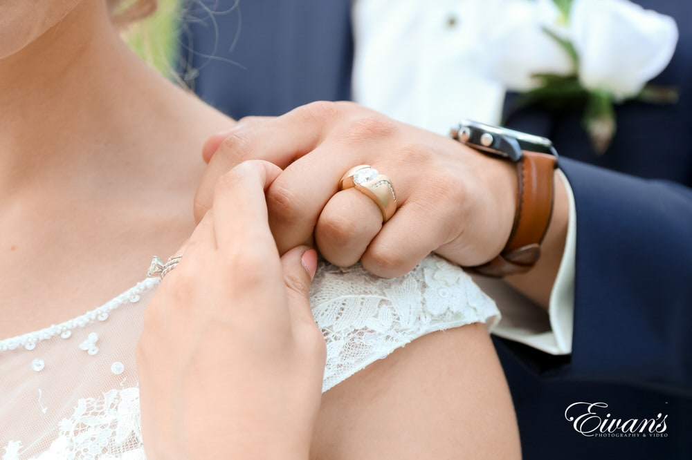 The bride and groom stand together while also showing off the new ring that will forever solidify their love.