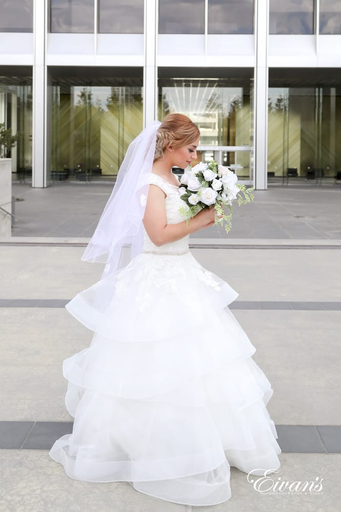 The bride stands beautifully in front of a shining and shimmering building having her elegant look radiating off the building.